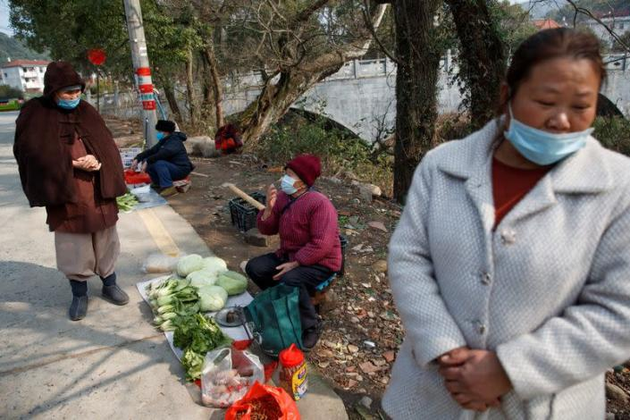 People wear face masks in a village outside Donglin Temple that is under lockdown because of the coronavirus outbreak in Jiujiang