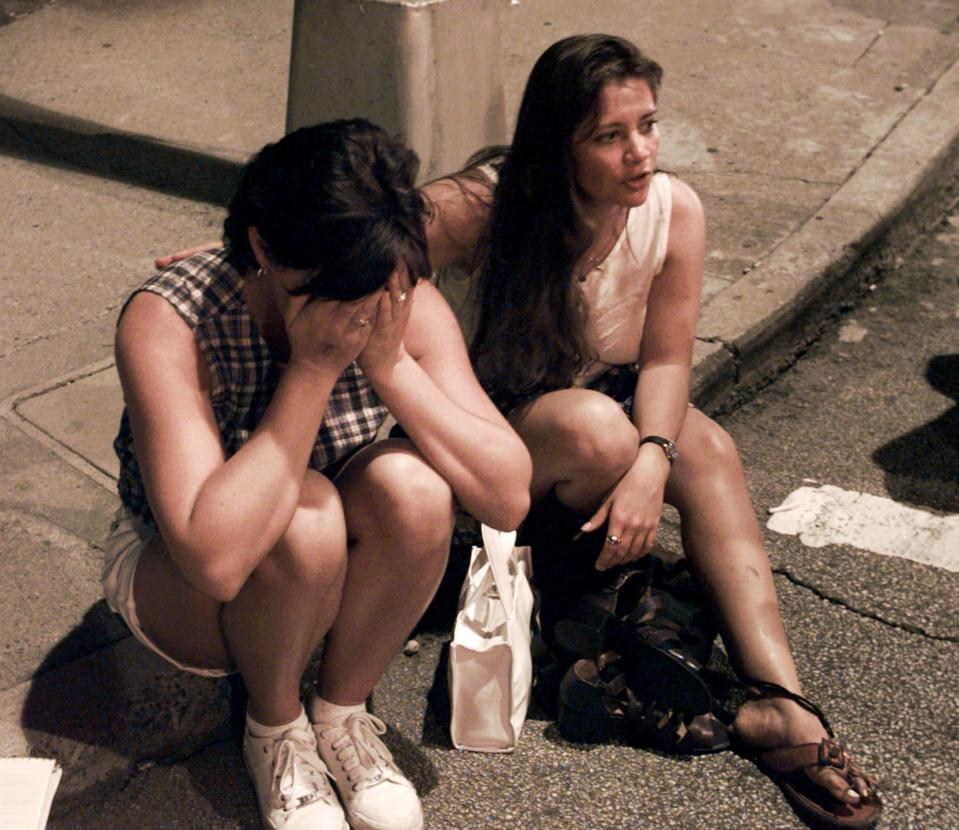 FILE - In this Saturday, July 27, 1996, file photo, Shelly Martin of Spokane, Wash., left, and Roselia Norwood of Hawaii react after an explosion occurred in Centennial Park in Atlanta during the 1996 Summer Olympics. (AP Photo/Doug Mills, File)
