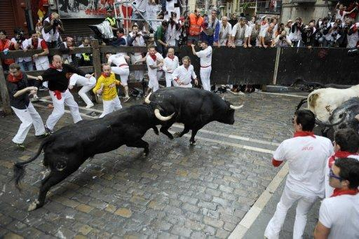 Participants run in front of Dolores Ybarra's bulls