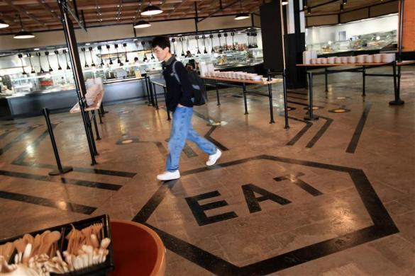 An employee walks through the cafeteria at the new headquarters of Facebook in Menlo Park, California January 11, 2012.