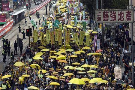 Thousands of pro-democracy protesters hold up yellow umbrellas, symbols of the Occupy Central movement, during a march in the streets to demand universal suffrage in Hong Kong February 1,2015. REUTERS/Tyrone Siu