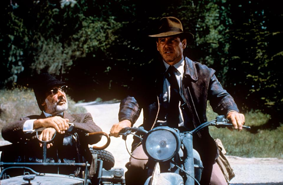 American actor Harrison Ford as archaeologist Indiana Jones riding the motorcycle in company of British actor Sean Connery as Prof. Henry Jones, Indiana's father, who gaves him a questioning look sitting on the sidecar, in a scene from the Indiana Jones and the Last Crusade. USA, 1989. (Photo by Mondadori Portfolio via Getty Images)