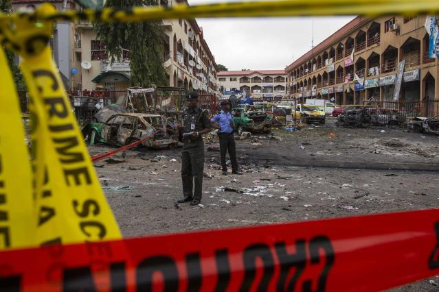 Nigerian police officers examine the scene of a bombing at the business district in Abuja June 26, 2014. At least 21 people were killed when a suspected bomb tore through a crowded shopping district in the Nigerian capital Abuja during rush hour on Wednesday, police said, adding to the toll of hundreds killed in attacks this year. (NIGERIA - Tags: CIVIL UNREST TPX IMAGES OF THE DAY)