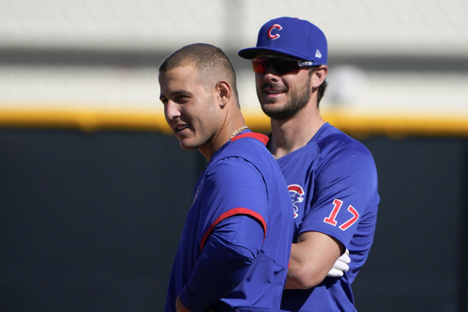 Chicago Cubs' Anthony Rizzo, left, and Kris Bryant stand on the field during a spring training baseball workout in Mesa, Ariz., Monday, Feb. 22, 2021. (AP Photo/Jae C. Hong)