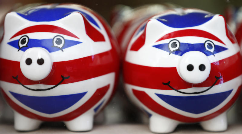 Smiling Union Jack piggy banks are lined up for sale in the window of a souvenir store on Oxford Street in central London January 20, 2014. Britain's financial services industry is beginning to feel the benefits of economic recovery, as firms report growth in profits, business volumes and optimism in the fourth quarter, according to a survey. Some 69 percent of firms said they felt more optimistic about the overall business situation versus just 1 percent who felt less optimistic, the quarterly CBI/PwC financial services survey showed on Monday. REUTERS/Andrew Winning (BRITAIN - Tags: POLITICS BUSINESS)