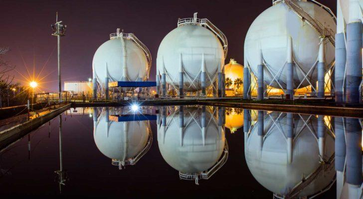 natural gas storage at night, storage facility reflected in pond
