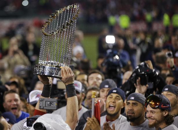 A player holds up the championship trophy after defeating the St. Louis Cardinals in Game 6 of baseball's World Series Wednesday, Oct. 30, 2013, in Boston. The Red Sox won 6-1 to win the series. (AP Photo/Matt Slocum)