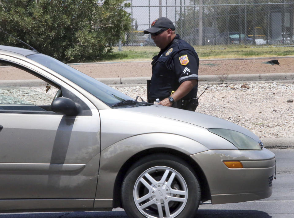 An El Paso police officer checks vehicles along a roadway near the scene of a shooting at a shopping mall in El Paso, Texas, on Saturday, Aug. 3, 2019. Several people were killed in the shooting Saturday in a busy shopping area in the Texas border town. (AP Photo/Rudy Gutierrez)