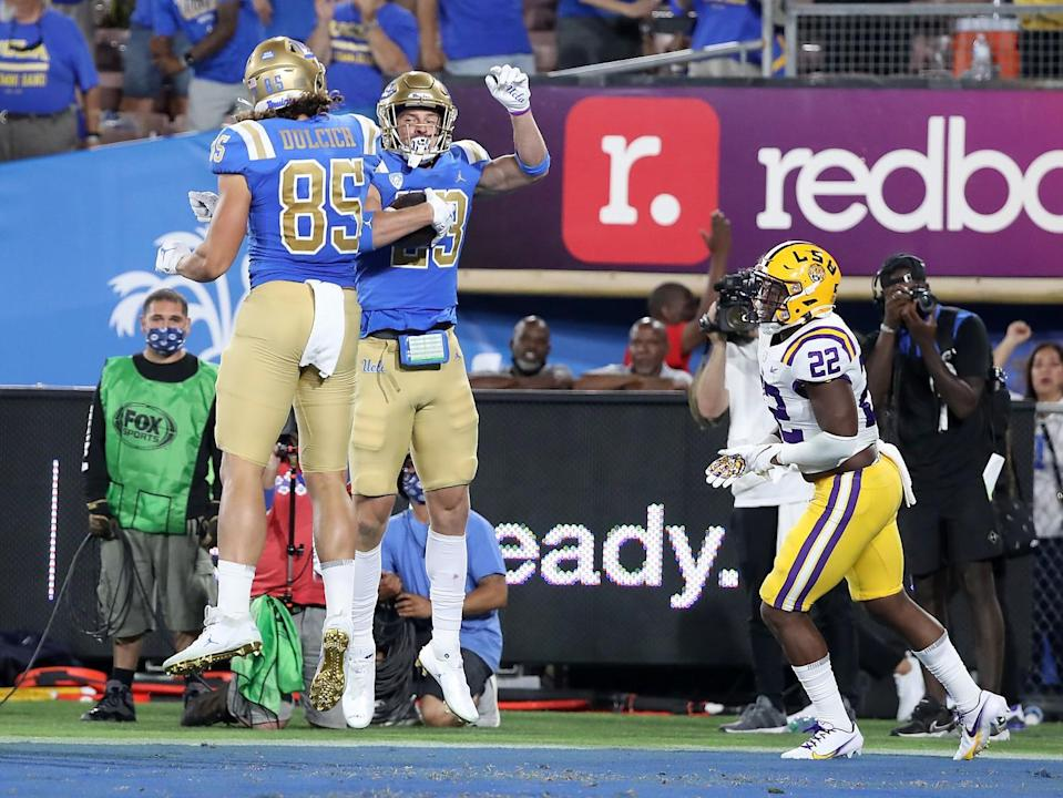 UCLA wide receiver Chase Cota (23) is congratulated by teammate Greg Dulcich.