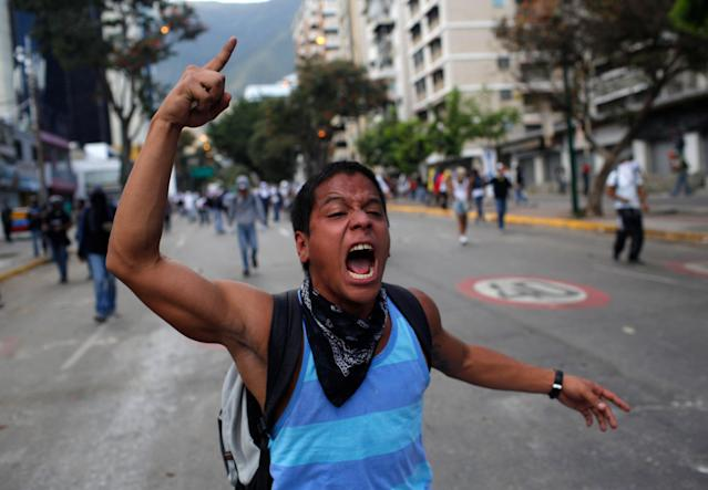 A demonstrator shouts slogans against Bolivarian National Guards during an anti-government protest in Caracas, Venezuela, Sunday, March 2, 2014. Since mid-February, anti-government activists have been protesting high inflation, shortages of food stuffs and medicine, and violent crime in a nation with the world's largest proven oil reserves. (AP Photo/Rodrigo Abd)