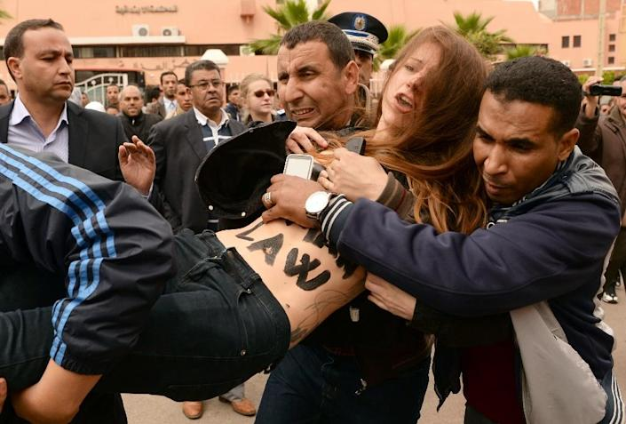 Undercover Moroccan police arrest a FEMEN activist outside the court in the central city of Beni Mellal on April 11, 2016 (AFP Photo/Fadel Senna)