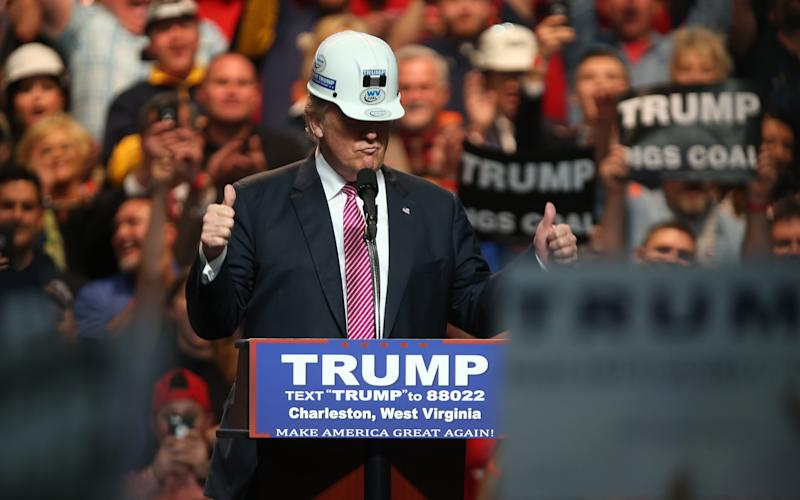 Republican Presidential candidate Donald Trump models a hard hat in support of the miners during his rally at the Charleston Civic Center on May 5, 2016 in Charleston, West Virginia. - Credit: Mark Lyons/ 2016 Getty Images