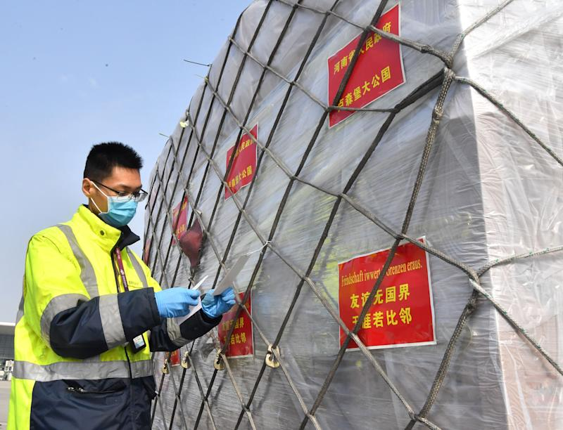 "ZHENGZHOU, March 22, 2020 -- A staff member prepares to load donated materials onto a cargo plane at Xinzheng International Airport in Zhengzhou, capital of central China's Henan Province, March 22, 2020. The first batch of medical supplies donated by China's Henan Province, including 500,000 surgical masks and 100,000 pairs of medical gloves, departed from Zhengzhou on Sunday for Luxembourg by direct airline along the ""Air Silk Road"" linking Luxembourg with Zhengzhou to help Luxembourg fight the COVID-19. (Photo by Li Jianan/Xinhua via Getty) (Xinhua/Li Jianan via Getty Images)"