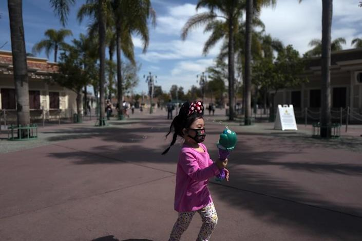 ANAHEIM, CA - MARCH 17: Wearing a face mask, Bliss Cordova, age 2 1/2, of Chino, runs around Downtown Disney chasing bubbles on Wednesday, March 17, 2021 in Anaheim, CA. More than a year after closing due to the pandemic, the theme parks at the Disneyland Resort in Anaheim are scheduled to open April 30 with limited capacity and restrictions on some attractions. (Francine Orr / Los Angeles Times)