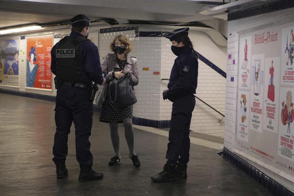 Policemen controls a commuters in the Paris subway, Friday, Oct. 30, 2020. France re-imposed a monthlong nationwide lockdown Friday aimed at slowing the spread of the virus, closing all non-essential business and forbidding people from going beyond one kilometer from their homes except to go to school or a few other essential reasons. (AP Photo/Thibault Camus)