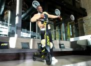 FILE PHOTO: Olympic gold medallist Usain Bolt poses for a photograph as he shows off an electric scooter at a launch event in Tokyo