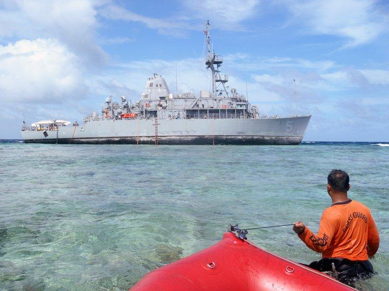 This photo, taken on January 22, 2013 by Philippine Coast Guard (PCG), shows a coast guard wading through water as he tugs a boat towards the US navy minesweeper, USS Guardian, which remains trapped at the Tubbataha reef off the western island of Palawan after it ran aground on January 17