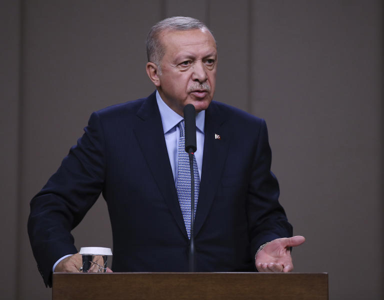 Turkish President Recep Tayyip Erdogan talks to reporters before traveling to Russia to meet with Russian President Vladimir Putin, in Ankara, Tuesday, Oct. 22, 2019. Erdogan says up to 1,300 Syrian Kurdish militia have yet to vacate areas in northeast Syria, as the clock a Turkish-U.S. cease-fire agreement runs. (Presidential Press Service via AP, Pool )