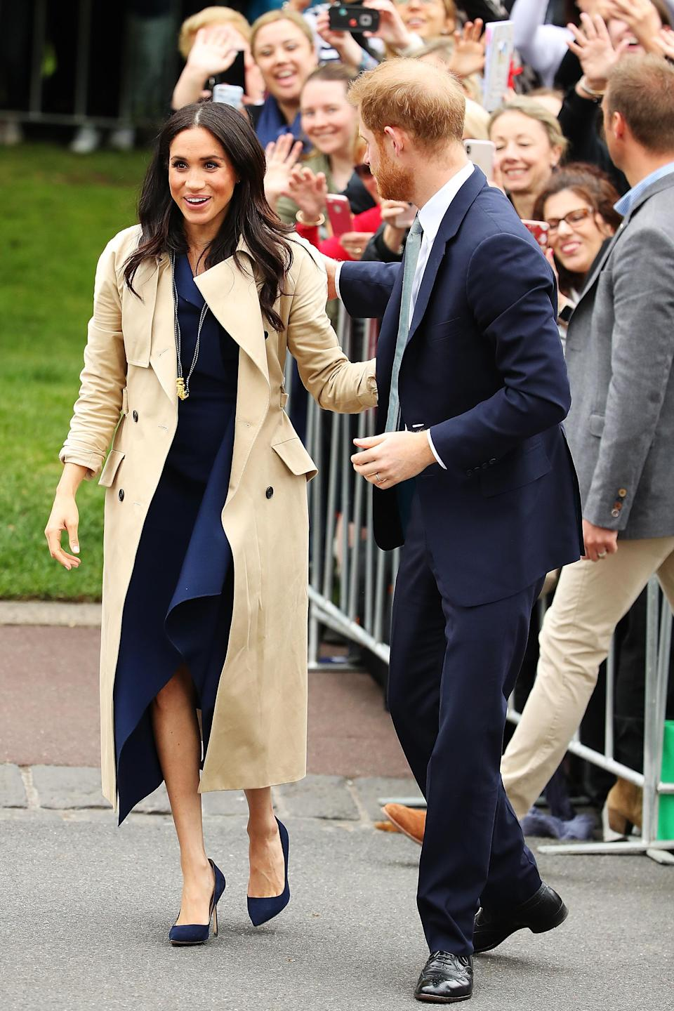 <p>Heading to Melbourne with her husband Prince Harry, the Duchess of Sussex opted for a classic navy frock by Australian designer Dion Lee. Photo: Getty </p>