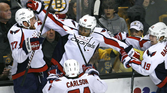 FILE - In this April 25, 2012, file photo Washington Capitals right wing Joel Ward, center, is congratulated by teammates after scoring the game-winning goal against the Boston Bruins during overtime in Game 7 of an NHL hockey Stanley Cup first-round playoff series in Boston. In 2014, then-Capitals forward Joel Ward was also the subject of racial social media posts after he scored a game-winning playoff goal. (AP Photo/Charles Krupa, File)