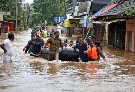 Rescuers evacuate people from a flooded area to a safer place in Aluva