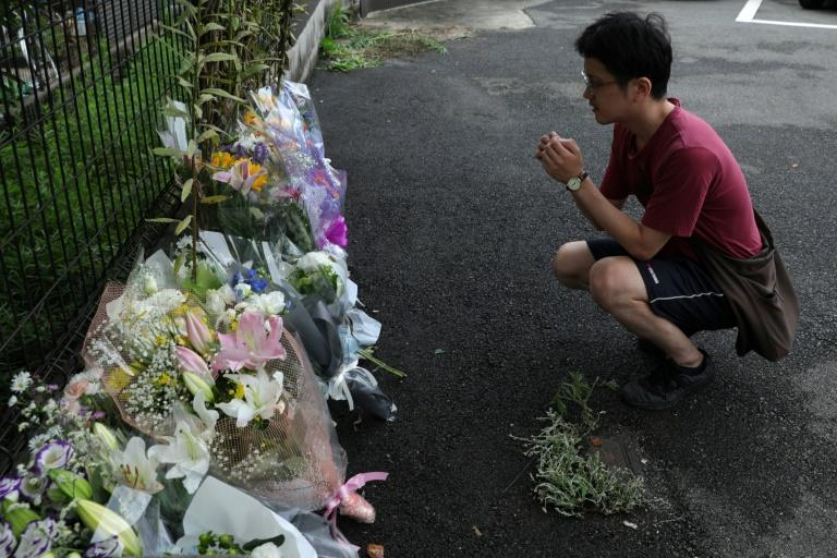A man prays next to flowers and tributes laid at the scene of a fire at the Kyoto Animation company building