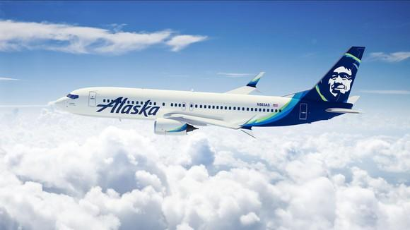 An Alaska Airlines airplane flying over clouds