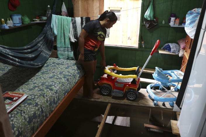 Valeria Ribeiro de Souza walks on a wooden plank that keeps furniture above floodwater inside her home in Anama, Amazonas state, Brazil, Thursday, May 13, 2021. (AP Photo/Edmar Barros)