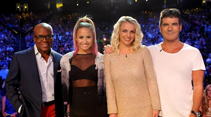 """This June 2012 photo released by FOX shows judges, from left, L.A. Reid, Demi Lovato, Britney Spears and Simon Cowell on the set of """"The X Factor."""" The contest between """"The Voice"""" and """"The X Factor"""" is escalating after NBC scheduled its """"Voice"""" against Wednesday's second-season debut of Fox's """"X Factor.""""  (AP Photo/FOX, Ray Mickshaw)"""