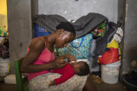A woman feeds her infant son in a shelter for internally displaced people due to violence, at a school converted into a shelter, in Port-au-Prince, Haiti, Tuesday, Sept. 14, 2021. Officials say the gangs' fight over territory in Port-au-Prince has forced hundreds of families to abandon burned or ransacked homes in impoverished communities, with many of them staying in gymnasiums and other temporary shelters that are running out of water, food and items like blankets and clothes. (AP Photo/Rodrigo Abd)