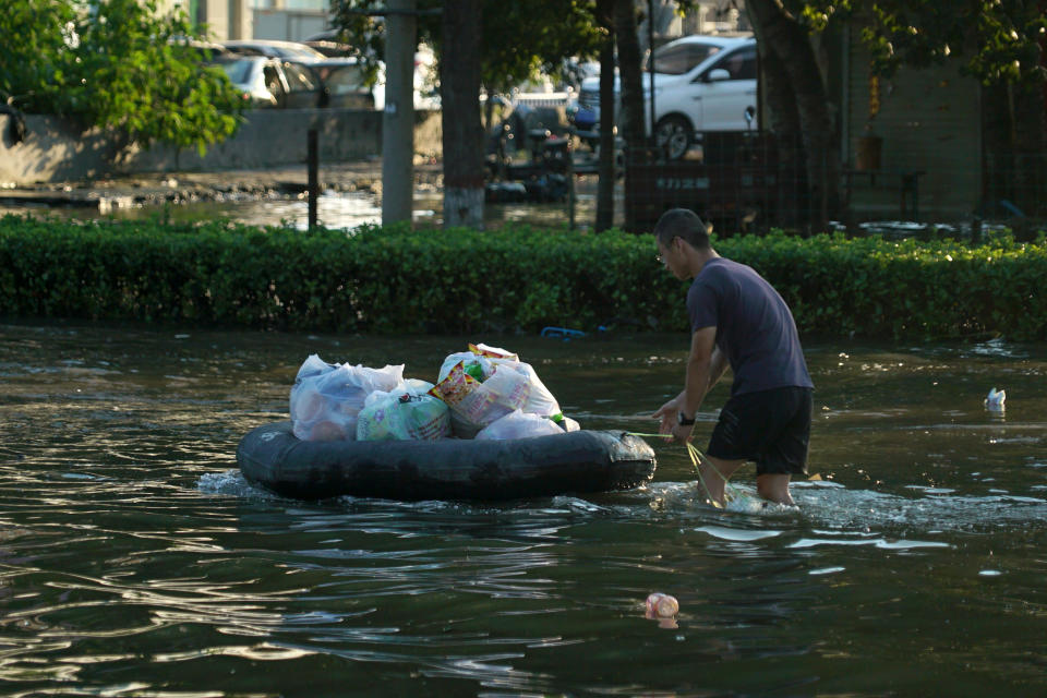 A man pushes an inflatable raft with supplies through floodwaters in Xinxiang in central China's Henan Province, Monday, July 26, 2021. Forecasters Monday said more heavy rain is expected in central China's flood-ravaged Henan province, where the death toll continues to rise after flash floods last week that killed dozens of people. (AP Photo/Dake Kang)
