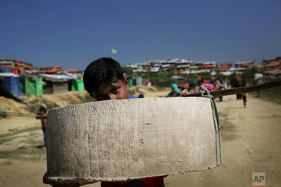 <p>A Rohingya Muslim boy carries concrete cylindrical material used to build latrines in Jamtoli refugee camp in Bangladesh. Since late August, more than 620,000 Rohingya have fled Myanmar's Rakhine state into neighboring Bangladesh, where they are living in squalid refugee camps. (AP Photo/Wong Maye-E) </p>