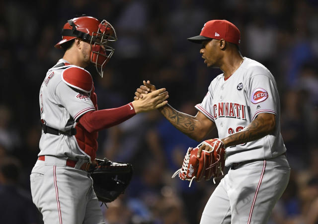 Cincinnati Reds closing pitcher Raisel Iglesias right, celebrates with catcher Kyle Farmer left, after defeating the Chicago Cubs in a baseball game Monday, July 15, 2019, in Chicago. (AP Photo/Paul Beaty)
