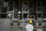 FILE - In this Feb. 12, 2020, file photo, workers in hazmat suits work at a water treatment facility at the Fukushima Dai-ichi nuclear power plant in Okuma, Fukushima prefecture, northeastern Japan. The head of the wrecked Fukushima nuclear plant said Tuesday, March 2, 2021 there's no need to extend the current target to finish its decommissioning in 30-40 years despite uncertainties about melted fuel inside the plant's three reactors. (AP Photo/Jae C. Hong, File)