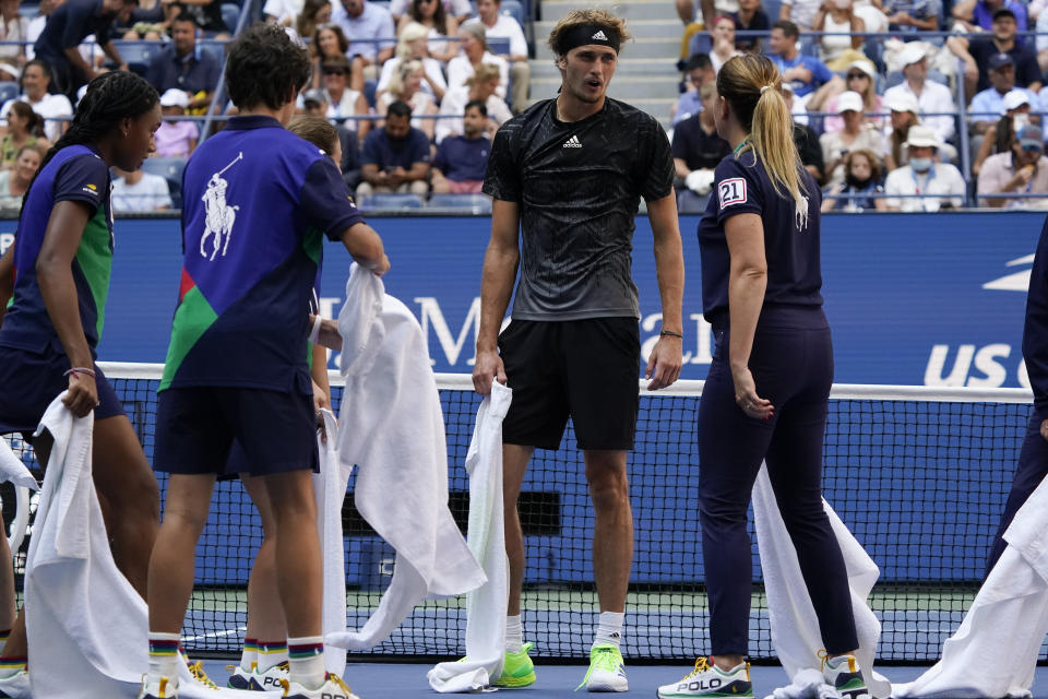 Alexander Zverev, of Germany, talks with court attendants as they dry liquid off the court during the quarterfinals of the US Open tennis championships against Lloyd Harris, of South Africa, Wednesday, Sept. 8, 2021, in New York. (AP Photo/Elise Amendola)