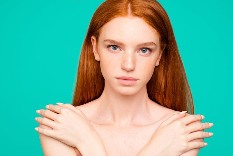 Redhead woman covering her chest in front of a turquoise blue background.
