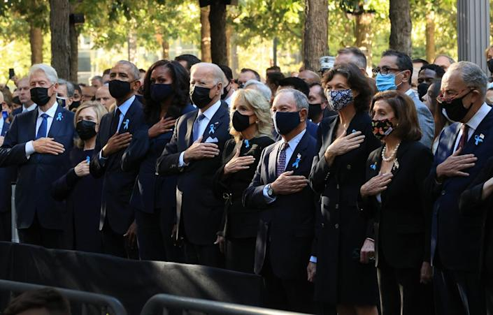 Current and former politcal leaders place their hands on their hearts and stand for the national anthem in New York City.
