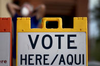A poll observer stretches outside a polling station on Election Day, early, Tuesday, Nov. 3, 2020, in Glendale, Ariz. (AP Photo/Matt York)