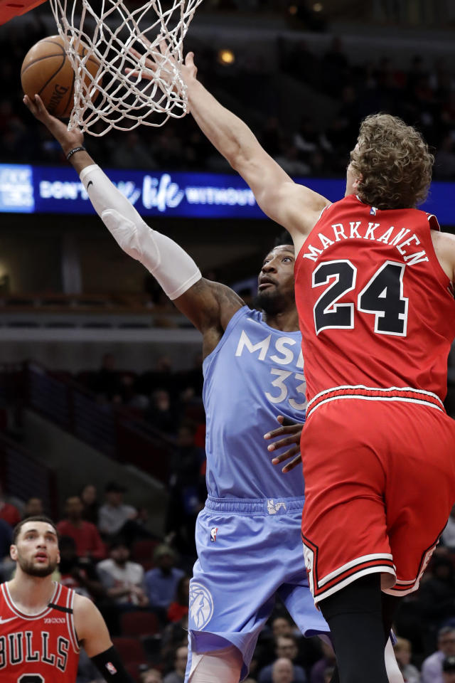 Minnesota Timberwolves forward Robert Covington, left, drives to the basket against the Chicago Bulls forward Lauri Markkanen during the first half of an NBA basketball game in Chicago, Wednesday, Jan. 22, 2020. (AP Photo/Nam Y. Huh)