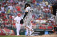 San Francisco Giants starting pitcher Johnny Cueto, center, walks to the dugout after he was pulled during the sixth inning of a baseball game against the Washington Nationals, Sunday, June 13, 2021, in Washington. (AP Photo/Nick Wass)