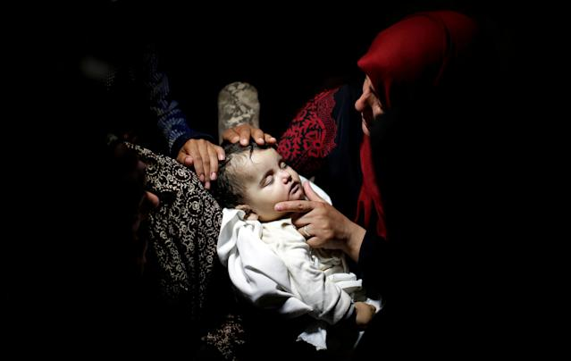 <p>A relative mourns as she carries the body of eight-month-old Palestinian infant Laila al-Ghandour, who died after inhaling tear gas during a protest against U.S embassy move to Jerusalem at the Israel-Gaza border, during her funeral in Gaza City, May 15, 2018. (Photo: Mohammed Salem/Reuters) </p>