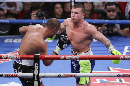Canelo Alvarez, right and Sergey Kovalev exchange punches during a light heavyweight WBO title bout, Saturday, Nov. 2, 2019, in Las Vegas (AP Photo/Isaac Brekken)