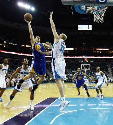 Golden State Warriors guard Klay Thompson (11) drives to the basket against New Orleans Hornets center Chris Kaman (35) in the first half of an NBA basketball game in New Orleans, Wednesday, March 21, 2012. (AP Photo/Gerald Herbert)