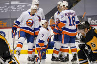 New York Islanders' Jordan Eberle (7) gets up from the ice as teammates gather around him after he scored against the Pittsburgh Penguins during the second period of an NHL hockey game, Saturday, Feb. 20, 2021, in Pittsburgh. (AP Photo/Keith Srakocic)