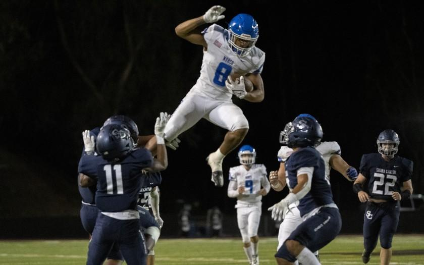 CALABASAS, CA - SEPTEMBER 24, 2021: Norco running back Jaydn Ott (8) tries to leap over Sierra Canyon defenders Darryl West (11) and Micah Valenzuela (10) in the first half at Calabasas High School at on September 24, 2021 in Calabasas, California.(Gina Ferazzi / Los Angeles Times)