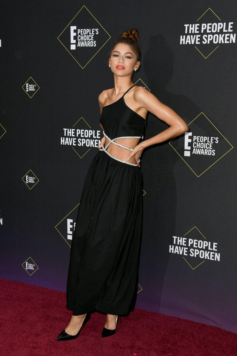 <p>She pulled up to the 2019 People's Choice Awards ready to show off some shoulder. This black gown from Christopher Esber also featured super cool metallic-trimmed cutouts.</p>
