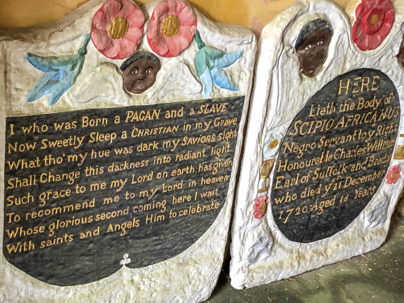 """Casts of the headstone and footstone of an enslaved African man, in the entrance to St Mary's church, in Bristol, England, Thursday June 18, 2020, where the memorial for an enslaved African man have been vandalised in St Mary's churchyard in an apparent """"retaliation attack"""" following the toppling of a statue of slave trader Edward Colston during anti-racist protests held in the wake of the killing of George Floyd in the US. The Grade II-listed, brightly painted memorial to Scipio Africanus have been smashed and a message was scrawled in chalk on flagstones nearby. (Ben Birchall/PA via AP)"""