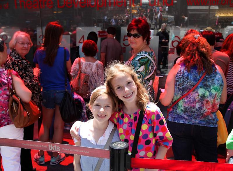 This June 19, 2013 photo shows Maggie Patrick, 7, left, and her sister Sophie Patrick, 9, outside the famous TKTS booth in Times Square in New York. The girls were there after school with family members to get discount tickets to a matinee. (AP Photo/Mark Kennedy)