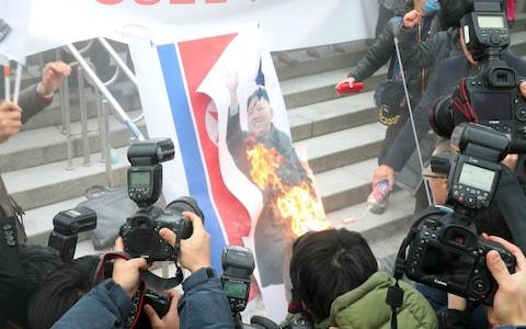 South Korean protestors burn a picture of North Korean leader Kim Jong-Un during an anti-North Korea rally outside Seoul station - Credit: AFP PHOTO / Dong-A Ilbo