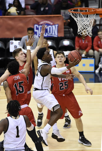 Wofford guard Tray Hollowell (21) goes up for a basket between VMI forward Myles Lewis (15) and forward Tyler Creammer (25) in the first half of an NCAA college basketball game for the Southern Conference basketball tournament championship, Saturday, March 9, 2018, in Asheville, N.C. (AP Photo/Kathy Kmonicek